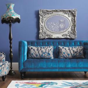 Fotel w kwiaty będzie równie efektowną dekoracją co bukiet kwitnących roślin. Zestawiony z sofą w aksamitnym obiciu stworzy delikatną, romantyczną aranżację. Fot. Very.