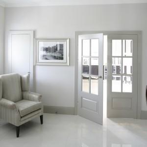 Jasny hol spaja cały dom. Tutaj również dominuje klasyczna elegancja. Połyskująca podłoga odbija światło wpadające przez okrągłe przeszklenie. Projekt: Alexander James Interiors. Fot. Bartosz Jarosz.