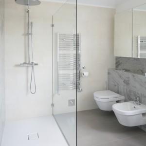 Ulokowaną na tle jasnokremowej ściany przestrzeń prysznica od strefy sanitariatów oddziela duża tafla szkła. Projekt: Alexander James Interiors. Fot. Bartosz Jarosz.