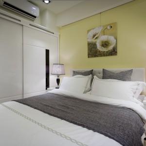 Jedną ze ścian w sypialni wykorzystano na wbudowanie dużej, pojemnej garderoby. Przestrzeń wykorzystano do maksimum, dzięki przesuwnym drzwiom, zamiast tradycyjnie otwieranych skrzydeł. Projekt i zdjęcia: Moon Refined Design.