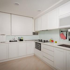W kuchni dominuje biel. Fronty mebli nie mają uchwytów, ale minimalizm został przełamany delikatnym frezowaniem. Ściana nad blatem ma delikatny, pastelowo-seledynowy kolor. Projekt i zdjęcia: Moon Refined Design.