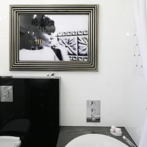 Portret kobiety w postarzanej ramie dodaje aranżacji charakteru. Do wykonania okładzin wykorzystano kilka rodzajów materiałów - płytki, mozaikę i szkło w achromatycznych barwach. Projekt: Małgorzata Galewska. Fot. Bartosz Jarosz.