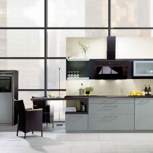 Wysoki sufit i meble kuchenne w chłodnej szarości pasują znakomicie do kuchni w stylu industrialnym. Fot. Brigitte.