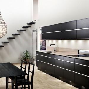 Proste, minimalistyczne fronty w ciemnym kolorze ozdobiono poziomymi, długimi, stalowymi uchwytami. Stal i czerń idealnie wpisuje się w industrialny klimat, potęgowany przez metalowy abażur wokół żarówki wiszącej nad stołem oraz schody bezpośrednio otwarte na kuchnię i wysoki sufit pomieszczenia. Fot. Ballingslov, linia Ek Svartbets.