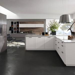 Proste meble kuchenne w chłodnych odcieniach bieli i szarości, w połączeniu ze stalowym abażurem lampy kuchennej i ciemnoszarą, matową podłogą. Fot. Alno, program Alnoshape i Alnosund.