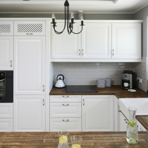 Białą zabudowę kuchenną z klasycznymi frezowaniami frontów oraz eleganckimi abażurami ocieplają drewniane blaty. Projekt: Beata Ignasiak. Fot. Bartosz Jarosz