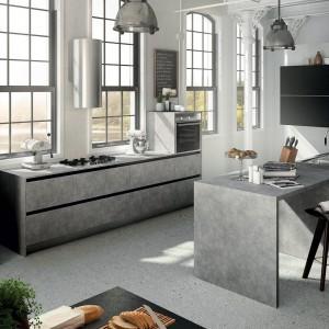 Niezwykle efektowne meble w kolorze melanżowej szarości, sprawiają wrażenie wykonanych z betonu. Wraz z loftowymi lampami tworzą elegancką, przemysłową aranżację. Fot. Municchi Cucine, kolekcja Skipper.