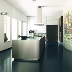 Satynowa, metaliczna wyspa kuchenna wprowadza do tej eleganckiej, minimalistycznej kuchni, delikatnie przemysłową atmosferę. Fot. Bulthaup.