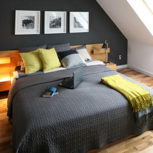 Ciemnoszara ściana w sypialni na poddaszu sprawia, że aranżacja jest elegancka i stonowana. W tej samej kolorystyce jest także narzuta na łóżko. Dla równowagi, szafki nocne i podłogę wybrano w kolorze jasnego drewna. Projekt: Luiza Jodłowska. Fot. Bartosz Jarosz.