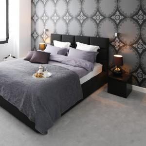 Piękna tapeta z motywem delikatnej koronki stanowi efektowne tło dla nowoczesnego łóżka tapicerowanego czarną tkaniną. Szara pościel i wykładzina podłogowa podkreślają nowoczesny wygląd wnętrza .Projekt: Magdalena Smyk. Fot. Bartosz Jarosz.