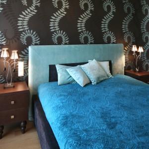Ściana za łóżkiem z dekoracyjnym motywem wyznaczyła charakter tej sypialni. Błękitny, tapicerowany zagłówek oraz turkusowa pościel wprowadzają do wnętrza odprężający klimat. Projekt: Agnieszka Ludwinowska. Fot. Bartosz Jarosz.