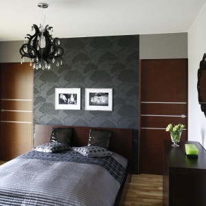 Tę sypialnię zdominowały ciepłe brązy, w formie mebli i forniru na ścianie. Delikatnie ochładza je dekoracyjna, szara tapeta oraz narzuta w tym samym, minimalistycznym kolorze. Projekt: Anna Gruner. Fot. Bartosz Jarosz.