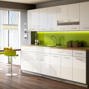 Dolna zabudowa została delikatnie wysunięta względem górnego rzędu szafek, co nadaje przestrzeni dynamizm, a z praktycznego punktu widzenia, pozwala na montaż większego zlewozmywaka, i bardziej funkcjonalny, szerszy blat. Zabudowę jednorzędową zamyka dobudowany blat, mogący posłużyć za niewielką jadalnię. Fot. Stolkar, kuchnia Luxe Blanco.