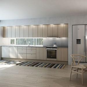 Zabudowę wpasowano we wnękę w ścianie, do maksimum przesuwając ją do środka powstałej przestrzeni, dzięki czemu w ścianie można było zamontować oświetlenie. Oryginalnie potraktowany aneks kuchenny zyskał bardzo nowoczesny charakter. Fot. Sigdal, kuchnia Amfi.