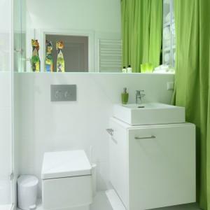 Niewielka, ale bardzo funkcjonalna łazienka. Po lewej stronie mamy prysznic, po prawej zaś miejsce na przechowywanie. Zamiast tradycyjnych drzwi właściciele zdecydowali się zieloną zasłonę, która dodatkowo pięknie ożywia jasną łazienkę. Projekt: Katarzyna Mikulska-Sękalska. Fot. Bartosz Jarosz.