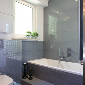 W tej łazience zastosowano rozwiązanie wielofunkcyjne - wanna i prysznic w jednym. Wnętrze niewielkiej łazienki powiększają również błyszczące płytki. Projekt: Arkadiusz Grzędzicki. Fot. Bartosz Jarosz.