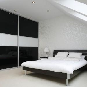 Połyskujące fronty szafy optycznie powiększają przestrzeń sypialni. Biały, szeroki pas umieszczony na środku dodaje lekkości czarnej zabudowie. Projekt: Magdalena Wielgus-Biały, Jacek Biały. Fot. Bartosz Jarosz.