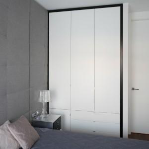 Białe, matowe fronty zabudowy podkreślono za pomocą czarnej ramy. Oba kolory świetnie pasują do dominującej w tej sypialni szarości. Projekt: Anna Maria Sokołowska. Fot. Bartosz Jarosz.