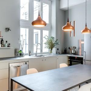 Efektowne lampy nad stołem jadalnianym pełnią funkcję zarówno praktyczną, jak i dekoracyjną. Ich ciepła barwa wprowadza do wnętrza element przytulności. Projekt: Tatiana Nicol. Fot. Meero Photographe Immobilier.