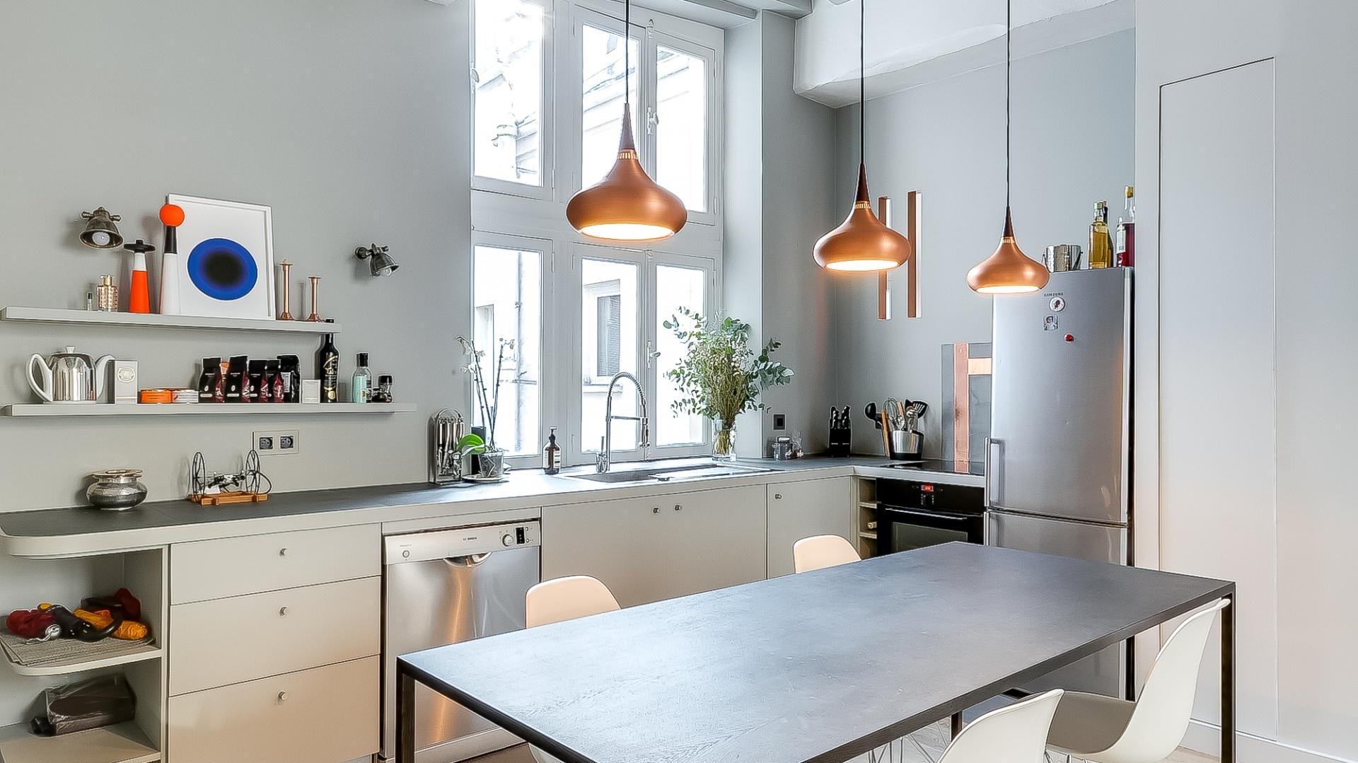 Odsłonięte i pomalowane na biało belki stropowe nadają przestrzeni delikatnie industrialny charakter. Projekt: Tatiana Nicol. Fot. Meero Photographe Immobilier.
