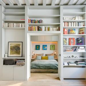Belki stropowe zdają się przechodzić w prostopadłe linie, tworzące półki na ścianie wokół drzwi, prowadzących z salonu do sypialni. Urządzono na nich biblioteczkę. Projekt: Tatiana Nicol. Fot. Meero Photographe Immobilier.