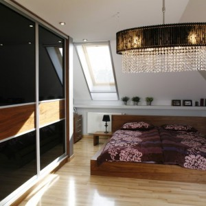 Fronty szafy zostały podzielone na trzy części. Środkowy pas w kolorze orzechowym przełamuje czarną, połyskującą powierzchnię. Pas na zabudowie nawiązuje do koloru łóżka. Projekt: Anna Gruner. Fot. Bartosz Jarosz.