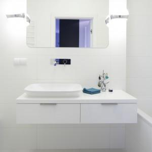 Białe ściany, biała szafka, biała ceramika, białe oświetlenie. Wszystko w jednym kolorze. Taką aranżację można szybko ożywić dodatkami. Każdego dnia może być inna. Projekt: Maciejka Peszyńska-Drews. Fot. Bartosz Jarosz.