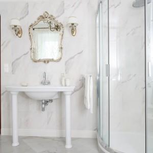 Strefa umywalki została pięknie wyeksponowana. Lustro w złotej, ozdobnej ramie i kinkiety w tej samej stylistyce potęgują jeszcze  wrażenie luksusu. Podobnie zresztą jak płytki imitujące marmur, którymi wykończone są zarówno ściany, jak i podłoga. Projekt: Małgorzata Goś. Fot. Bartosz Jarosz.