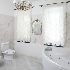 Łazienka zaprojektowana została w klasycznym stylu. Jest elegancka i daje poczucie luksus. Przy oknie umieszczona została duża, narożna wanna z hydromasażem, natomiast kabina prysznicowa z deszczownią znajduje się w przeciwległym rogu, obok umywalki. Projekt: Małgorzata Goś. Fot. Bartosz Jarosz.