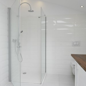 Szklana kabina prysznicowa i niski brodzik nadają przestrzeni łazienki nowoczesny charakter. Doskonale pasują również do bieli i drewna. Projekt: Konrad Grodziński. Fot. Bartosz Jarosz.