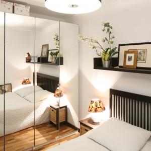 Szklane fronty optycznie powiększają przestrzeń niewielkiej sypialni. Mają też zastosowanie bardziej praktyczne. Doskonale spełniają rolę lustra. Projekt: Marcin Lewandowicz. Fot. Bartosz Jarosz.