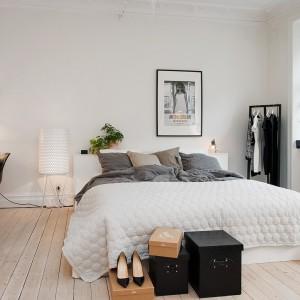 W tej sypialni urządzonej w skandynawskim stylu drewniana podłoga o jasnym wybarwieniu ociepla białe wnętrze. Powiększa również przestrzeń sypialni. Fot. Alvhem Mäkler.