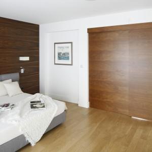 Szafę w sypialni utrzymano w kolorze drewna i schowano za solidnymi drzwiami, chowającymi się w ścianie. Projekt: Kamila Paszkiewicz. Fot. Bartosz Jarosz.