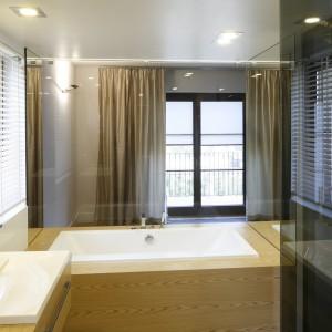 Duża ilość szkła podkreśla nowoczesny styl łazienki, nadając jej jednocześnie luksusowy charakter. Drewno w kolorze dębu efektownie ociepla przestrzeń. Projekt: Kamila Paszkiewicz. Fot. Bartosz Jarosz.