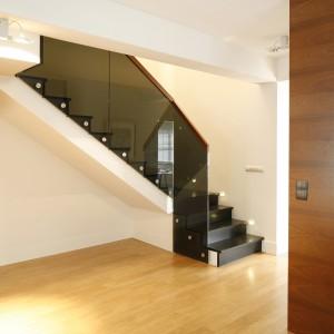 Ciemne stopnie schodów efektownie kontrastują z jasną konstrukcją je podtrzymującą i ciepłym kolorem drewna na podłodze. Projekt: Kamila Paszkiewicz. Fot. Bartosz Jarosz.