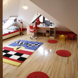 Podłogę wyłożona ciepłymi panelami zdobią dekoracyjne dywany, tworząc tematyczną aranżację powierzchni. Projekt: Anna Gruner. Fot. Bartosz Jarosz.