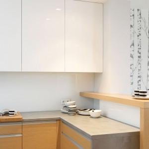 Białą ścianę pokryto taflą przeźroczystego szkła. Delikatna, subtelna powierzchnia idealnie komponuje się z białą górną zabudową i szarym blatem. Projekt: Beata Kruszyńska. Fot. Bartosz Jarosz.