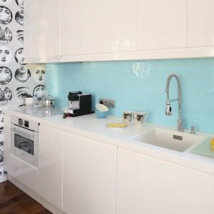 Białe meble kuchenne wykończone na wysoki połysk, dopełnia połyskująca powierzchnia szkła polakierowanego na delikatny, błękitny kolor. Projekt: Anna Maria Sokołowska. Fot. Bartosz Jarosz.