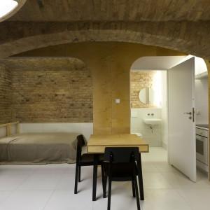 We wspólnej, otwartej przestrzeni mieszkania znalazło się miejsce na strefę sypialni, urządzoną w sąsiedztwie łazienki. Projekt: Mili Młodzi Ludzie. Fot. PION.