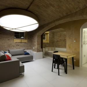 Niewielką ilość naturalnie wpadającego do wnętrz światła, rekompensuje duża lampa-słońce, zamontowana w centralnym punkcie mieszkania. Projekt: Mili Młodzi Ludzie. Fot. PION.