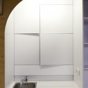 Proste, minimalistyczne fronty wykonane z białej melaminy scalono ze ścianą. Projekt: Mili Młodzi Ludzie. Fot. PION.