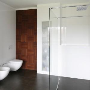 Kontrast do białej łazienki wprowadza ciemna podłoga i drewniane elementy na ścianie. Projekt: Piotr Stanisz. Bartosz Jarosz.