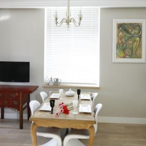 Delikatnie stylizowany stół na cztery osoby koresponduje z klasycyzującą komodą i barokowym żyrandolem. Lekkości meblowi nadaje jego jasny kolor i towarzyszące my białe krzesła. Projekt: Monika Gorlikowska. Fot. Bartosz Jarosz.