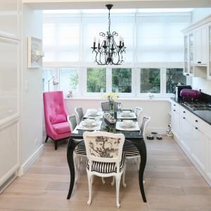 Stylizowany, niewielki stół stanowi centrum kuchni. Czarny kolor tonują białe krzesła z czarno-białym obiciem. Wykończenie na połysk dodaje meblowi lekkiego wyrazu. Projekt: Małgorzata Galewska. Fot. Bartosz Jarosz.