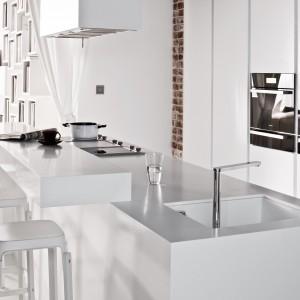 Wysoka zabudowa w białym kolorze stanowi estetyczne tło dla ciemnych sprzętów AGD, wbudowanych w mebel. Biała jest również wyspa i towarzyszące jej hokery, a nawet podwieszany zlewozmywak. Fot. Zajc Kuchnie.