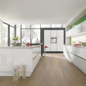 Meble kuchenne z minimalistycznymi, gładkimi frontami wykończonymi na wysoki połysk idealnie wpisują się w nowoczesny charakter tej kuchni. Biel pięknie harmonizuje z zielonymi ścianami. Fot. Wellmann, meble z programu G888 Vitus.