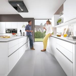 Gładkie i matowe fronty mebli nadają tej nowoczesnej kuchni elegancki charakter. Ciekawie uformowana bryła mebla, z blatem zdającym się unosić nad szafkami, dodaje kuchni futurystycznego wyrazu. Fot. Nobilia.