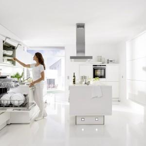 W tej kuchni króluje biel - od podłogi po meble. Te z kolei utrzymano w nowoczesnym stylu, z gładkimi frontami i efektownym podświetleniem w korpusie wyspy. Fot. Nolte Kuechen, kolekcja Star 27W.