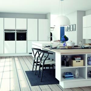 Elegancka biała kuchnia z frontami mebli w macie. Chłodną biel ocieplają drewniane elementy w postaci deski na podłodze i drewnianego blatu, wieńczącego dużą wyspę. Fot. HTH, model Glat Hvid.