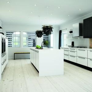 Zestawienie bieli i czerni oraz matowych powierzchni nadaje tej kuchni chłodny, elegancki charakter. Duże, poziome uchwyty zostały wyeksponowane na tle białych frontów i stanowią ich dekorację. Fot. HTH, model Sort Eg Laminat.